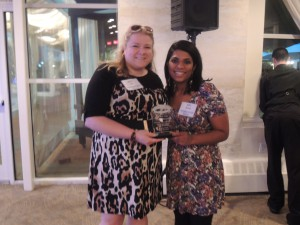 Christy Hinko, editor for Floral Park Dispatch and Hicksville Illustrated News/Westbury Times editor Betsy Abraham show off the first place trophy they received for Best Narrative: Home & Garden. (Photo by Dave Gil de Rubio)