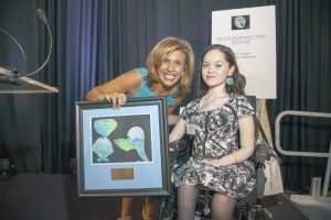 Tiffany, a student at Henry Viscardi School at The Viscardi Center, presenting Hoda Kotb with an original piece of artwork she created.