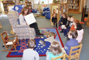 An integrated class attends story time with Mill Neck librarian Donna Argeroplos.