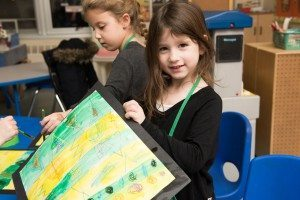 A student shows off the artwork she created at the SJJCC's afterschool program.