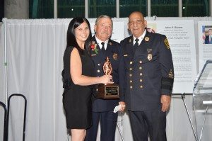 """From left: Nassau County Firefighters Museum Executive Director Alana Petrocelli; Honoree Chief John P. Brown receiving the """"Francis X. Pendl Firefighter Award""""; Museum Board President Angelo Catalano"""