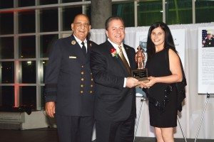 """From left: Museum Board President Angelo Catalano; Honoree Butch Yamali receiving the """"Firefighters Leadership Award""""; Nassau County Firefighters Museum Executive Director Alana Petrocelli"""