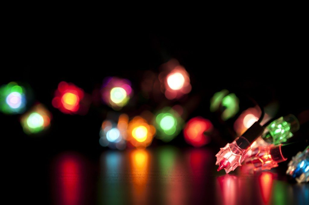Colourful Christmas lights with selectove focus, blur and reflections on a dark background with copyspace for your seasonal greetings