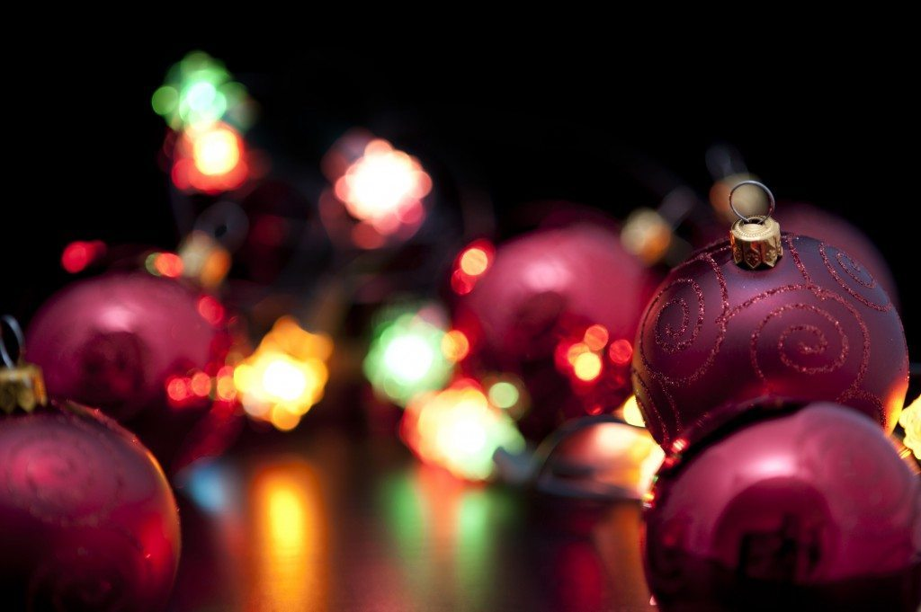 Brightly coloured party lights illuminating Christmas baubles and decorations in the foreground