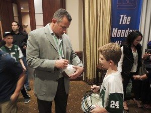 Former NFL quarterback Jay Fiedler, who played for the Jets in 2005, signs a ball for a young Darrell Revis jersey-clad fan. (Photos by Ben Strack)