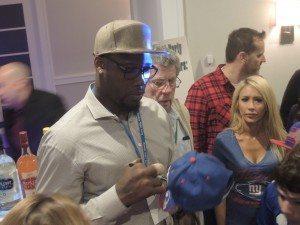 Fans surround Giants defensive end Jason Pierre-Paul as he signs hats, jerseys, helmets and footballs.