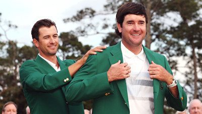 Adam Scott of Australia presents Bubba Watson of the United States with the green jacket after Watson won the 2014 Masters Tournament by a three-stroke margin on April 13, 2014 in Augusta, Georgia. (Photo by Andrew Redington/Getty Images)