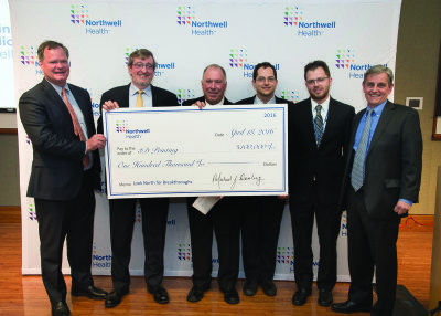 Michael J. Dowling, president and chief executive officer at Northwell Health, presented a check to researchers Daniel Grande, PhD, and Todd Goldstein of Northwell Health's Feinstein Institute for Medical Research and Lee Smith, MD, chief of pediatric otolaryngology at the health system's Cohen Children's Medical Center, to continue their research in 3D bioprinting.