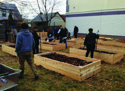 "Residents attend a community garden build and planting workshop at the ""Yes We Can"" Community Garden."