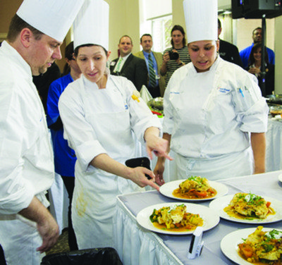 Winning chefs Patricia Sobel (center) of Northern Westchester does a last-minute check with her teammates about her entrée with Russel Ficke, Syosset Hospital; and Janisa Freysinet, North Shore University Hospital.