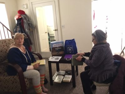 Volunteer Larissa Finik from The Blue Card delivers Hanukkah care package to Magda Rosenberg.
