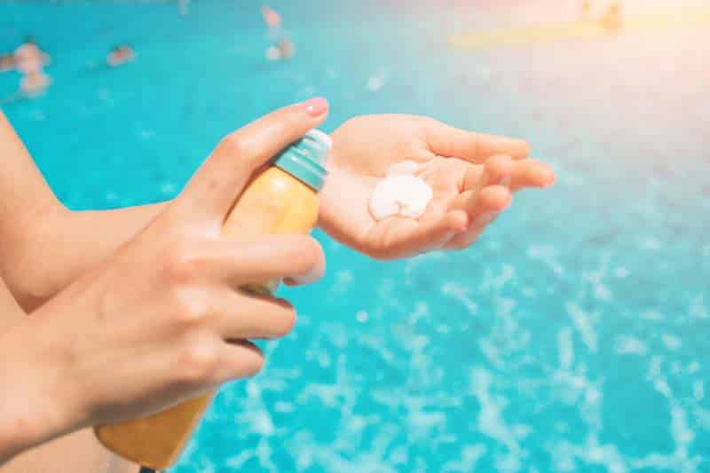 women standing on the beach and using suncream. close up of women hands receiving sunblock cream lotio.