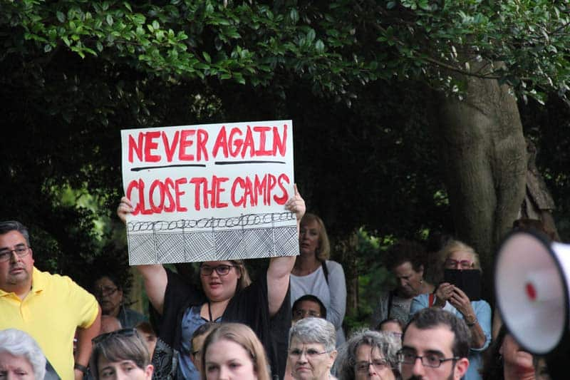 Woman holds sign that reads Never Again, Close The Camps