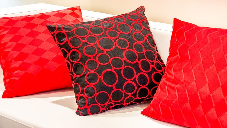 Two bright red pillows and a black and red one in the middle, all on a white sofa.
