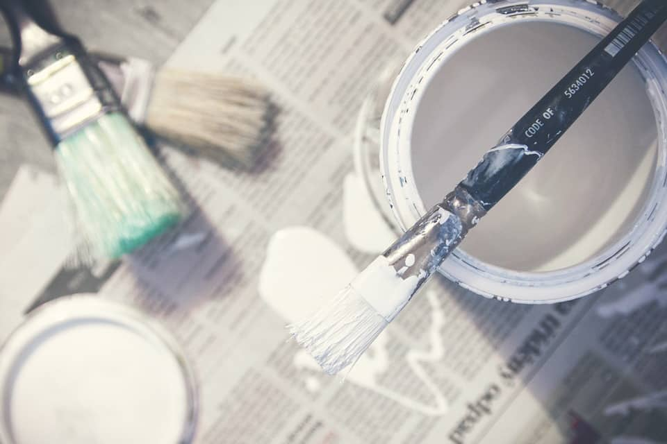 A brush and a bucket of white paint.